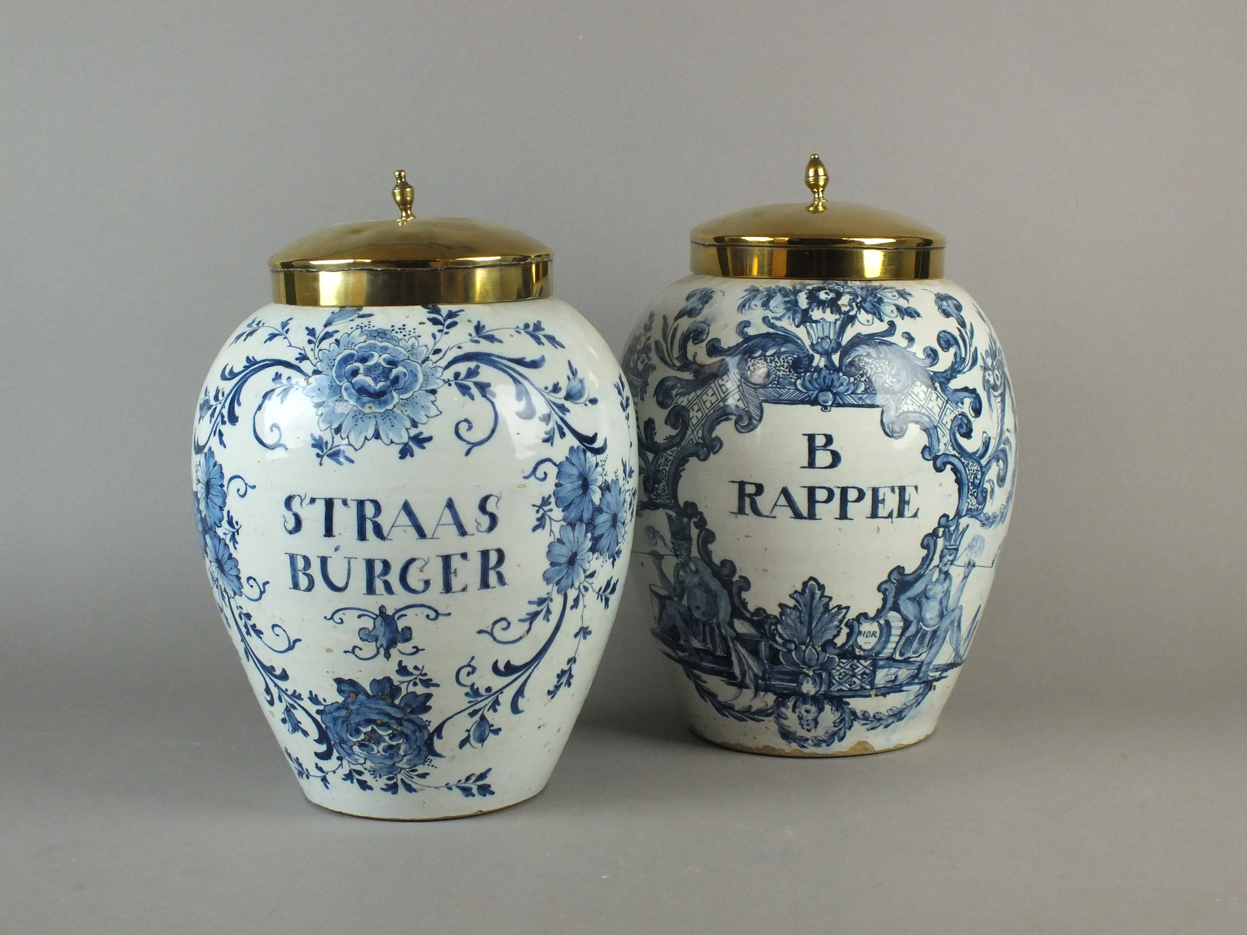 Two 18th century delft dry drugs jars Two large 18th century delft dry drug jars with copper covers, decorated in blue with inscriptions 'Straas Burger' and 'B Rapee' reserved against foliate grounds, painted blue PMV marks for Pieter Van Marksveld De Grieksche, 34cm high  Sold for £1,600