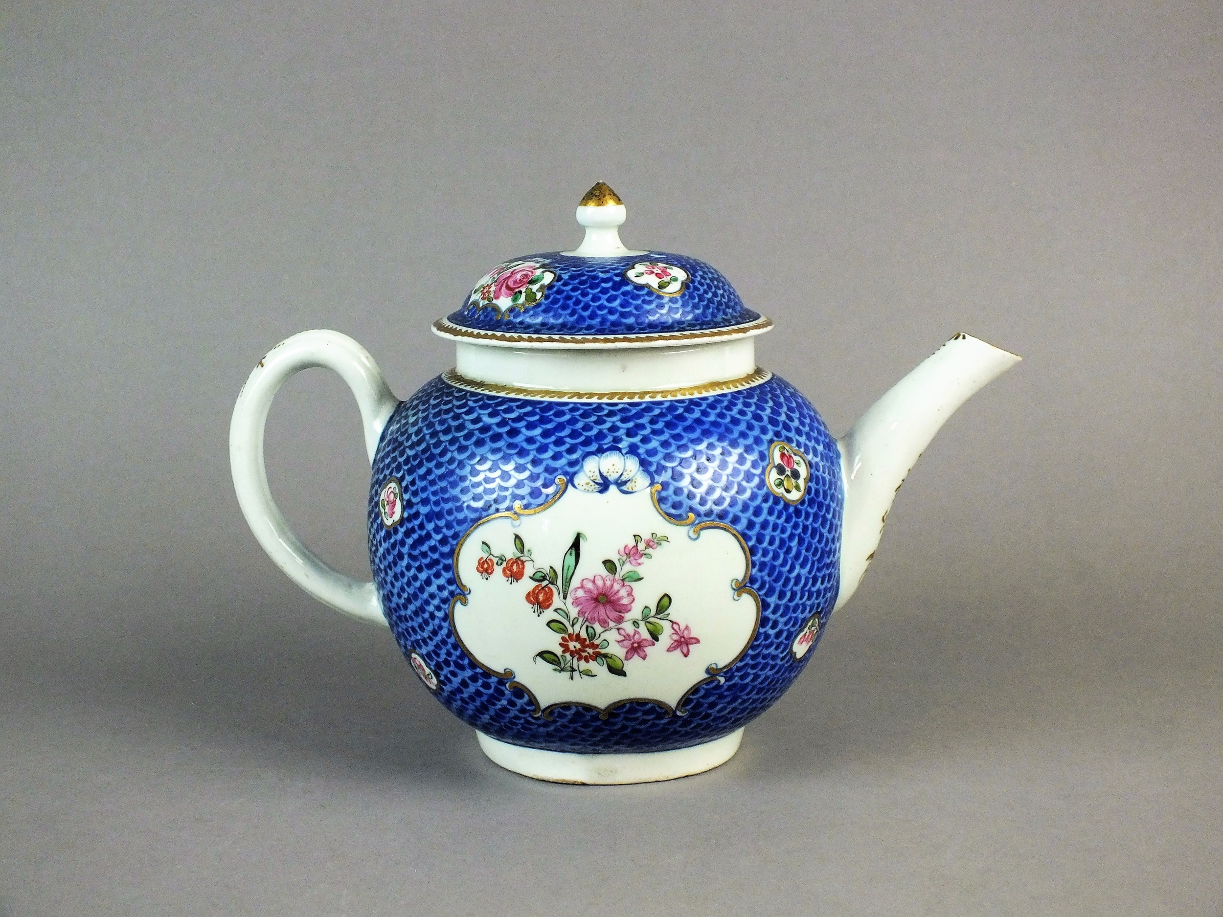 Lot 301: A Philip Christian & Co teapot and cover circa 1770-75 enamelled with flowers in shaped panels reserved on a bright blue scaled ground, handle and spout with gilt foliate decoration,  unmarked, 16cm high  Provenance: Ex. C E Hanley Collection - purchased from Simon Spero, 4th April 2001. Previously in the Rous Lench Collection. Illustrated: Maurice Hillis, Liverpool Porcelain 1756-1804, p.229. Cf. The Victoria and Albert Museum, Accession No. C.96-1957 for a cake plate in the same pattern. Previously sold at Woolley and Wallis in 2016. Estimate: £1,500 - £2,000
