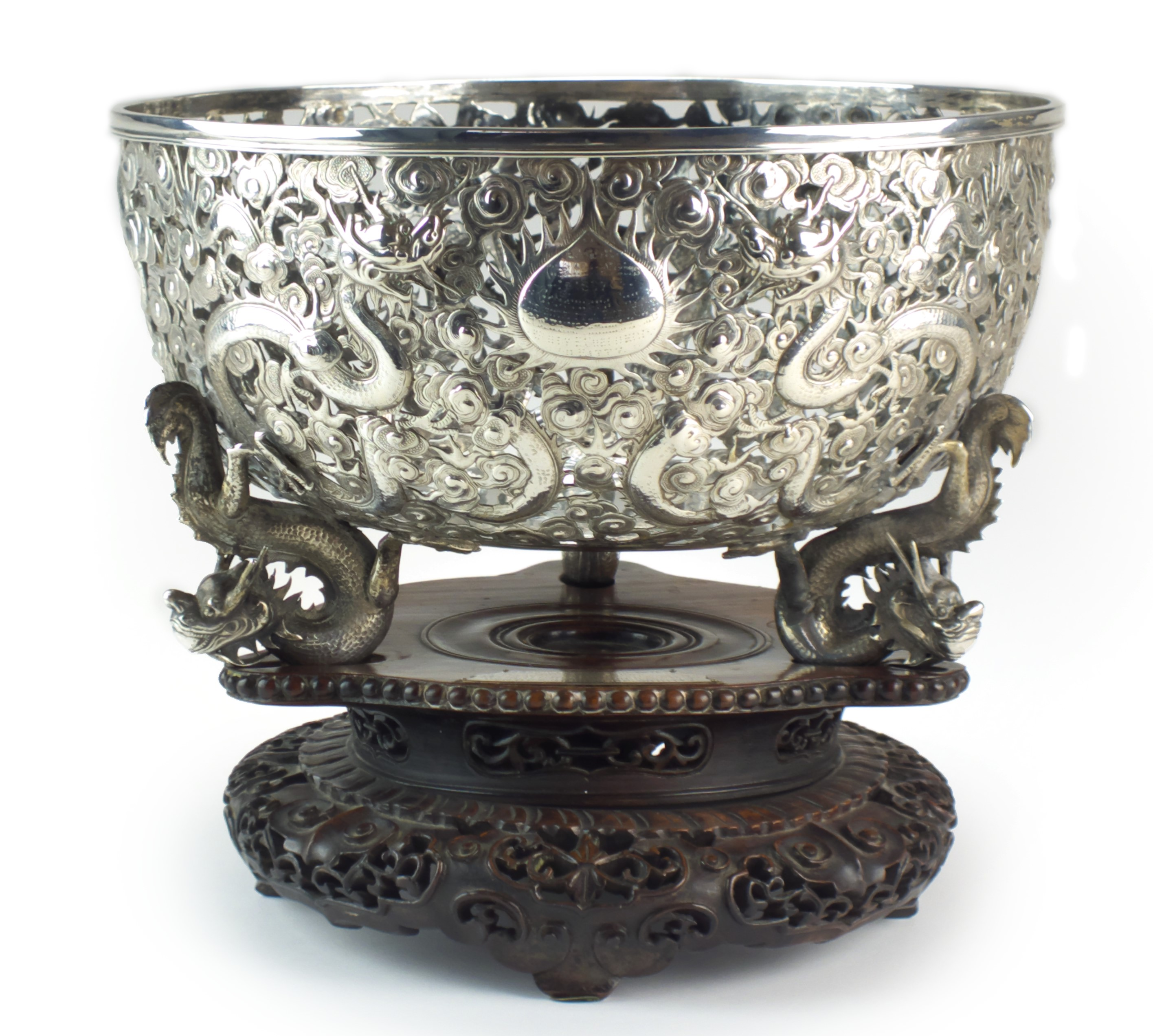 The Governor's Cup: A superb Chinese silver bowl by Wang Hing & Co, dated 1897, of rounded form and raised on three wrythen dragon feet, the openwork sides tooled and chased with multiple dragons in flight amid roiling clouds, a central flaming pearl cartouche inscribed 'Lagos (West Africa)