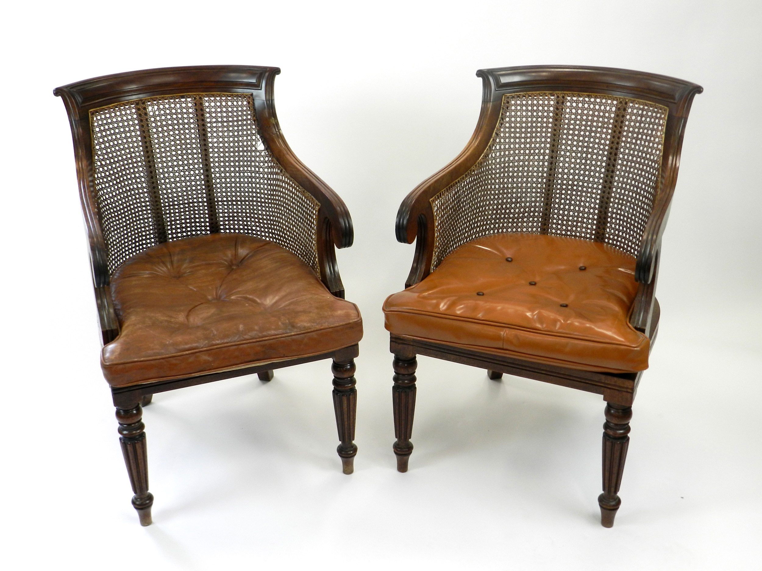A pair of mahogany bergere type armchairs, with reeded scroll arms and raised on fluted front supports, 54cm wide. (2)