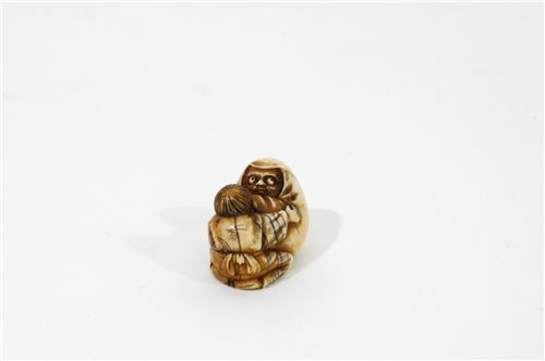 Lot 153 - A Japanese carved ivory netsuke of a boy and daruma doll