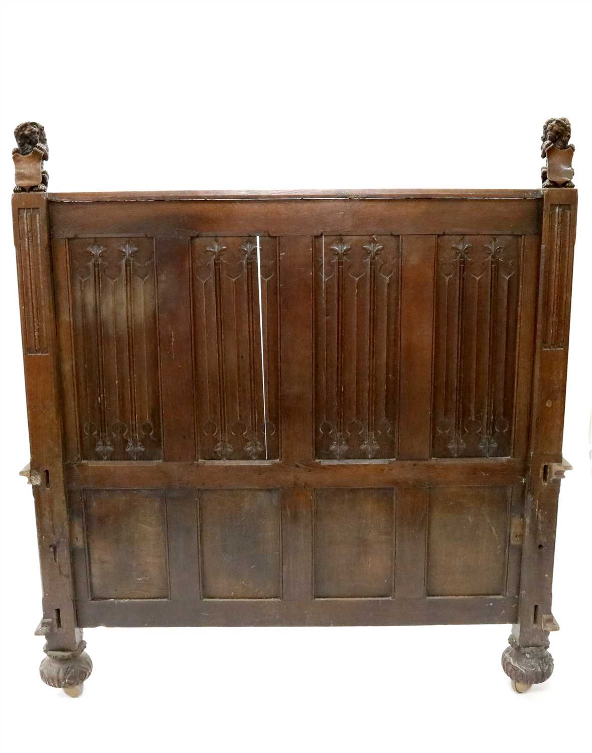 Lot 232-A large carved oak bed frame in the Old English style