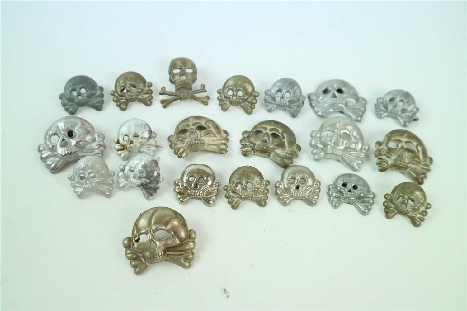 581 - Twenty one post-war SS-style skull badges