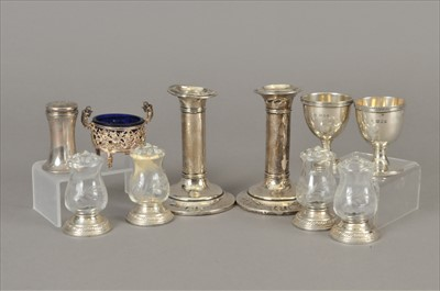 Lot 3-A pair of short silver candlesticks, together with two silver egg cups, a salt with blue glass liner, a pepperette and white metal mounted glass salt/pepper pots