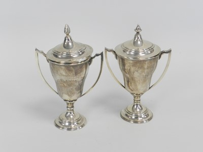 Lot 16 - A near pair of silver trophy cups and covers