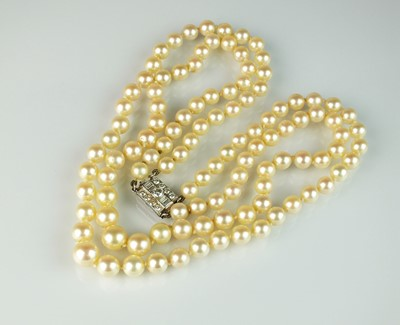 Lot 25 - A two strand graduated cultured pearl necklace with diamond set clasp