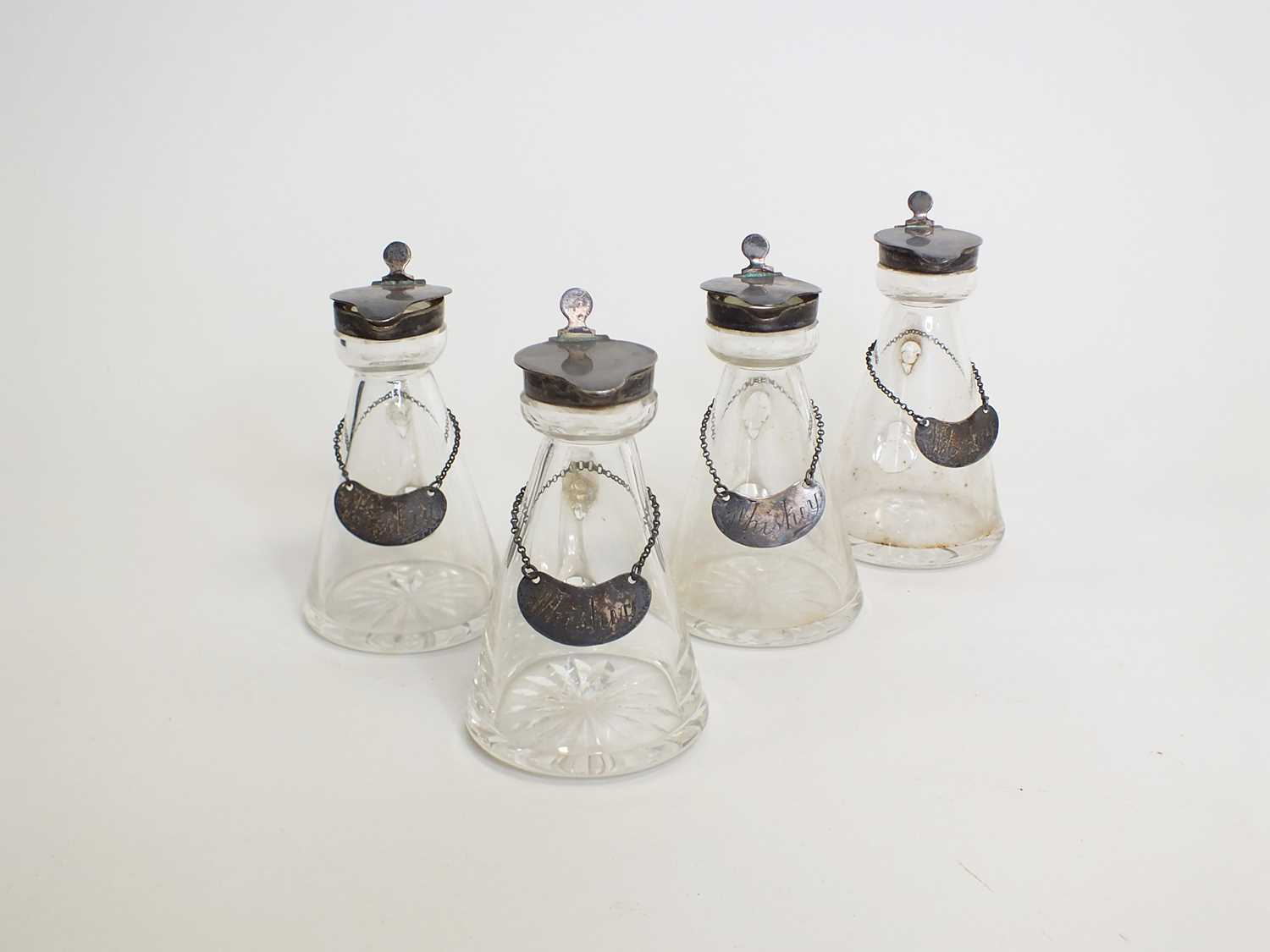Lot 11 - A set of four silver topped whiskey noggins and labels