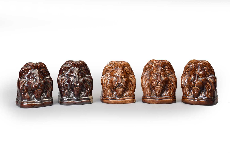 Lot 8 - Five treacle-glazed pottery lion-head sash window stops