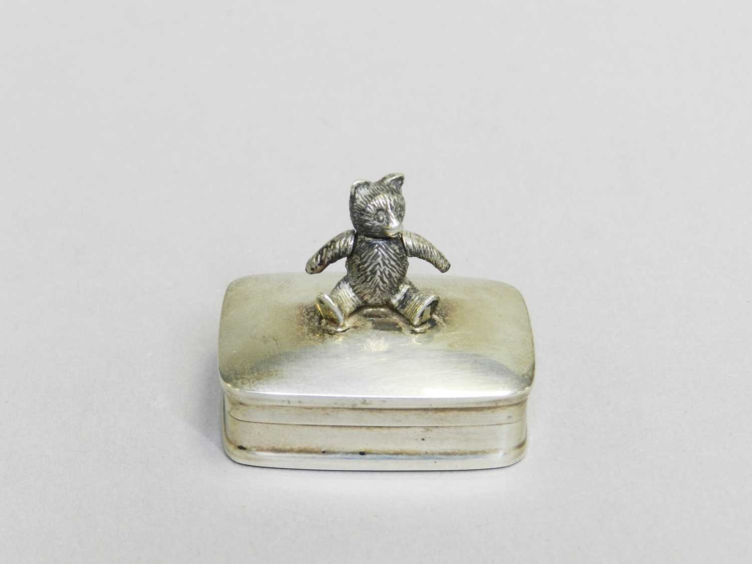 Lot 7 - A sterling silver pill box with teddy bear finial