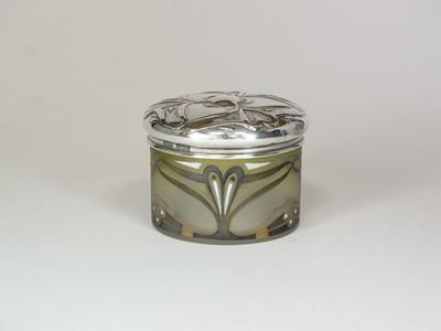 Lot 4 - An Art Nouveau silver topped glass dressing table jar