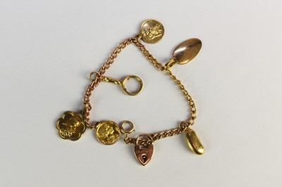 Lot 41 - A yellow metal curb link bracelet with charms
